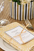 Menu tied to folded napkin with ribbon