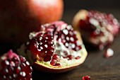 Whole and broken pomegranates on a dark surface