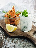 Prawns and herb yoghurt in glasses on a chopping board