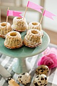 Miniature Bundt cakes with pink flags on green cake stand