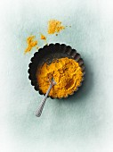 Ground turmeric in a tart tin with a spoon