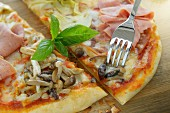 A pizza with turkey sausage, ham, mushrooms and artichokes