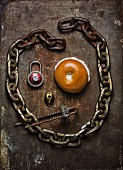 A face made from a bagel, an iron chain and a padlock