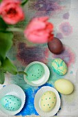Painted Easter eggs in and next to paper cake cases