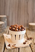 An arrangement of hazelnuts in a wooden basket
