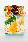 Herb leaves, vegetable chips and fruit slices on a tray (seen from above)