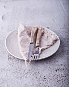 Rustic cutlery and a napkin on a plate