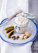 Tartar sauce in a jar on a plate with gherkins, capers and mushrooms