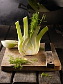 Fresh fennel, halved, on a wooden chopping board