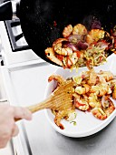 Fried prawns being transferred into a serving bowl