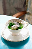Easter arrangement of quail egg, moss and feather in coffee cup