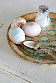 Variously painted Easter eggs, silver spoon and salt cellar on vintage tray