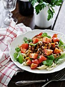 Pasta salad with minced meat, tomatoes and basil