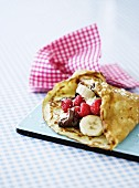 Crepe with raspberries, bananas, chocolate and coconut