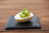 A devilled egg with spring onions