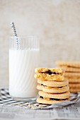 A stack of jam and cream biscuits with a glass of milk