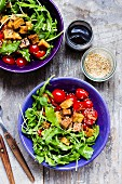 Rocket salad with sesame seed tofu and cherry tomatoes