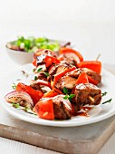 Barbecued meat skewers with red onions, peppers and herbs