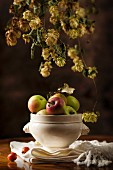 An autumnal arrangement featuring hops and apples
