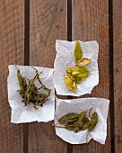 Fried sage and basil leaves on a pieces of paper on a wooden surface