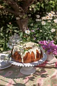 A Bundt cake with icing sugar on a garden table