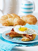A croissant with bacon and a fried egg