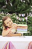 A girl in a garden next to a birthday cake decorated with colourful chocolate beans