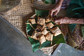 An Asian man making small packages from dried leaves
