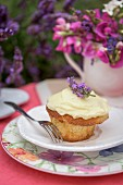An almond cupcake with lavender cream on a summer table outside