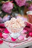 Raspberry meringues in a glass bowl on a table outside