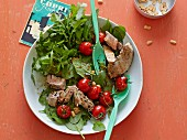Pulled tuna and braised tomatoes on a spinach salad