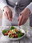 Greek salad being mixed