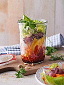 A layered Thai salad with mango and roast beef in a jar