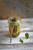 Wild herb salad with mango sauce in a jar