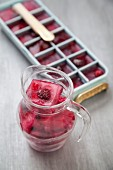 Berry ice cubes in an ice cube tray and in a glass jug