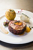 A pork collar steak filled with dried plums and blue cheese and served with a baked apple