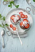 Chocolate muffins with strawberry jam and icing sugar