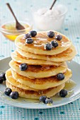 A stack of pancakes with honey and blueberries