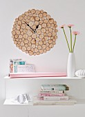 DIY wall clock made from round pieces of rustic birch wood above a stack of books and a vase of flowers on a white shelf