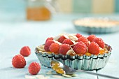 A raspberry tartlet with slivered almonds and jam