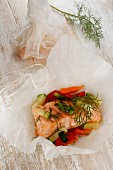 Salmon with colourful vegetables baked in parchment paper