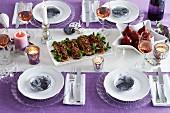Gedeckter Weihnachtstisch mit lila Tischdecke, verschiedenen Gerichten und Roséweingläsern