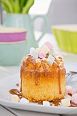 A mini sponge cake with caramel sauce and marshmallows