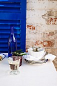 A glass of white wine on a table with a white tablecloth, stacked crockery, kalamata olives and a wine bottle in front of a royal blue wooden shutter