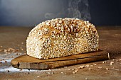 A steaming loaf of chia-spelt bread on a chopping board