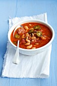 A stew with tomatoes, jalapeños, smoked pork belly, sausages and beans