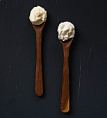 Two wooden spoons with sour cream and crème fraîche