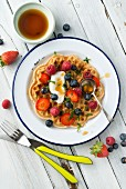 A vegan, gluten-free waffle with fresh berries, yoghurt and honey
