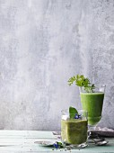 Two green smoothies garnished with borage and carrot leaves