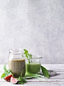 Two green smoothies garnished with figs and herbs
